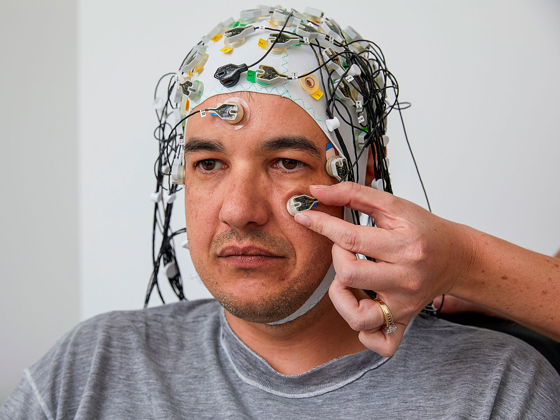 Marco Lopes, neuroscientist and operations lead at Neuroverse, dons an EEG cap and sensors to link his brain activity to a computer.