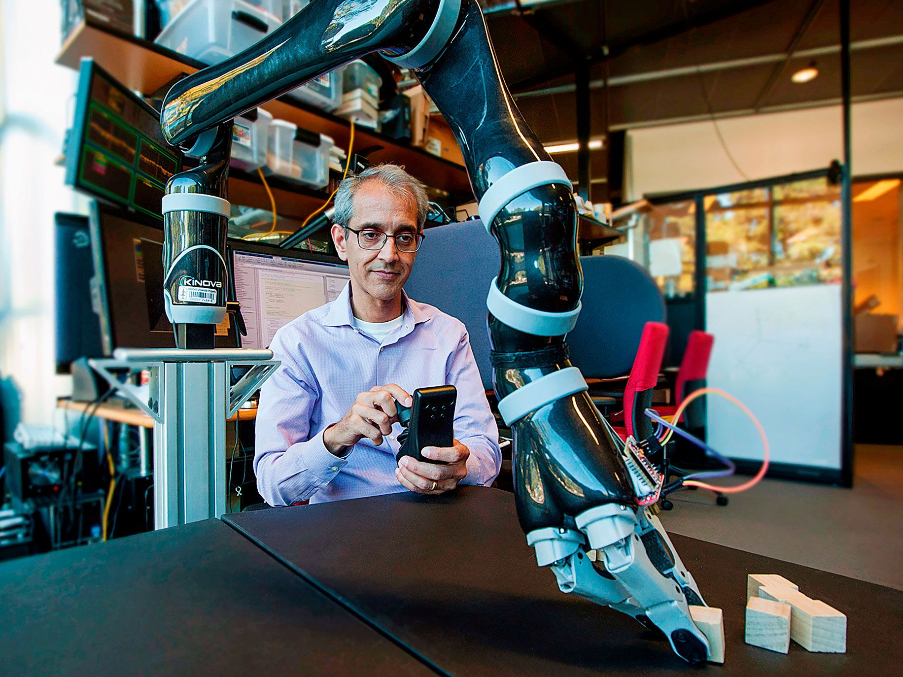 Krishna Shenoy, a pioneer of neural prosthetics at Stanford University, working with a robotic arm that uses a proximity detector to help it pick up a wooden block.