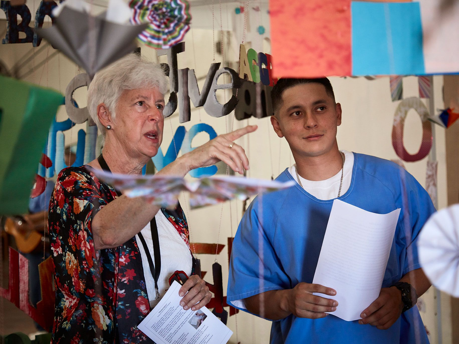 "Angel, one of the prisoner-artists at the California Institute for Men in Chino, shows a guest around the installation portion of the collaborative multidisciplinary performance piece ""Redemption."""