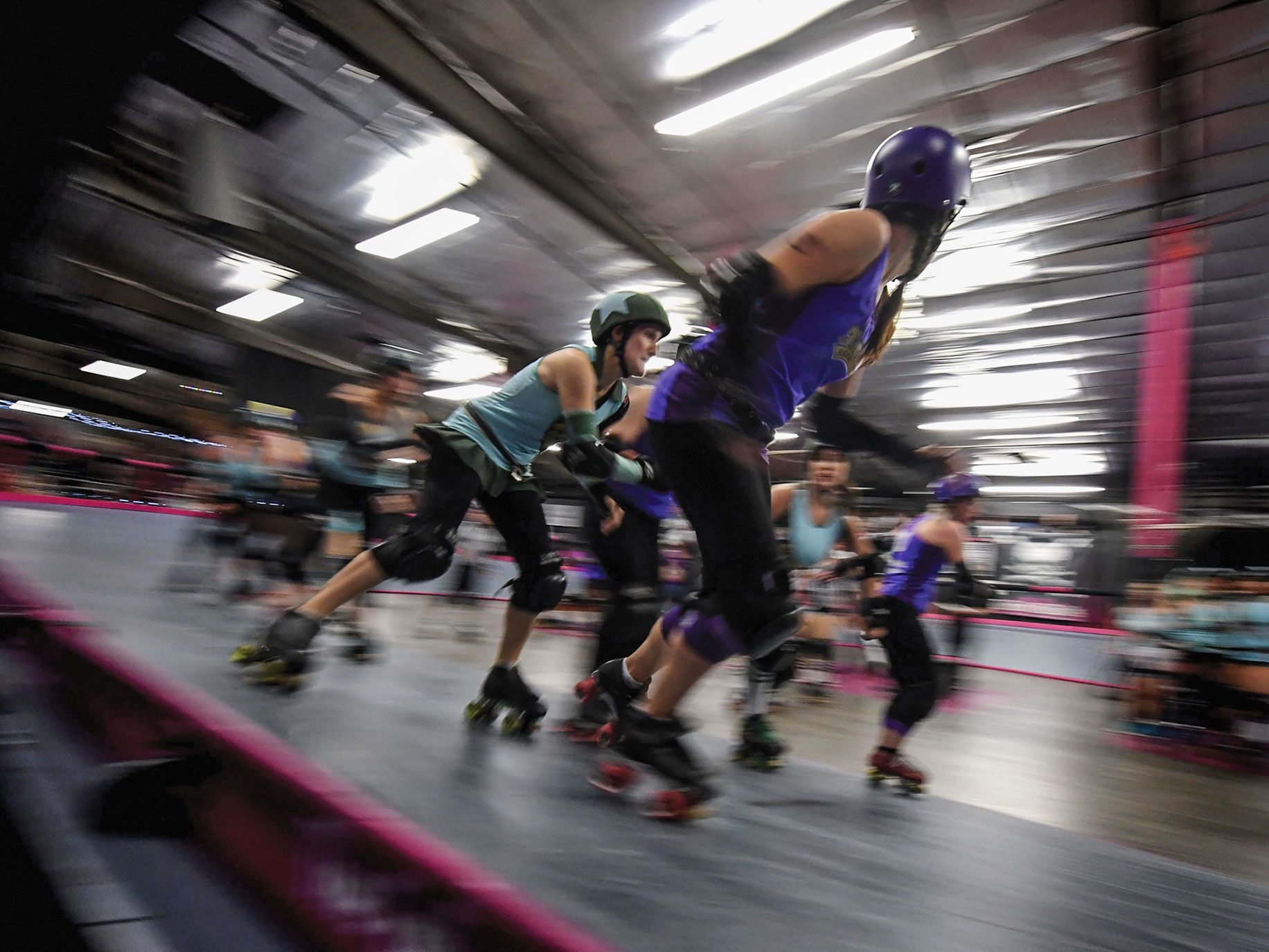 Members of the Varsity Brawlers team (purple tops) compete against the Tough Cookies team during a L.A. Derby Dolls women's banked track roller derby event in Los Angeles.