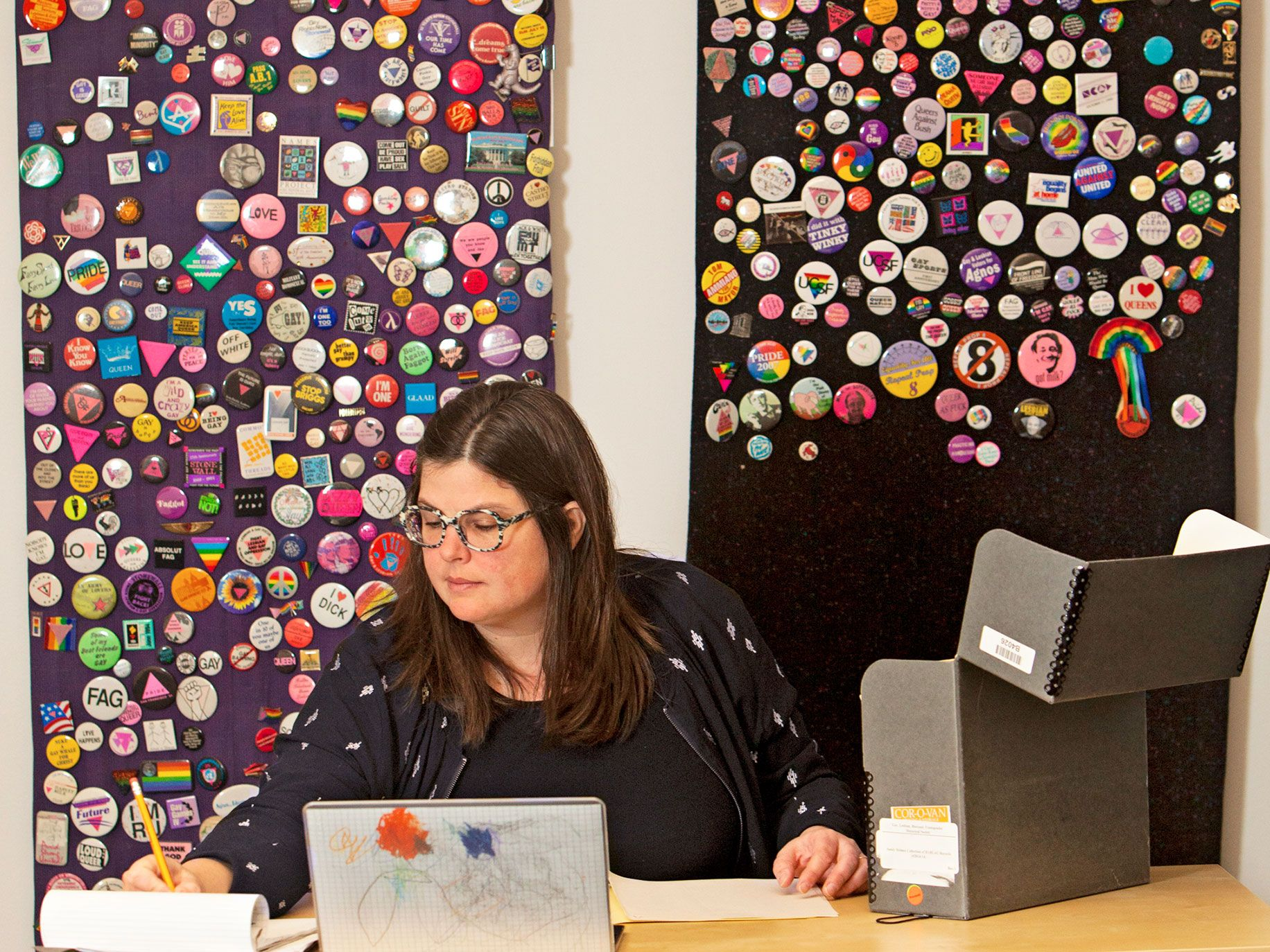 Researcher Christina Linden sits in front of a collection of GLBT buttons assembled by Michael Armanini at the museum.