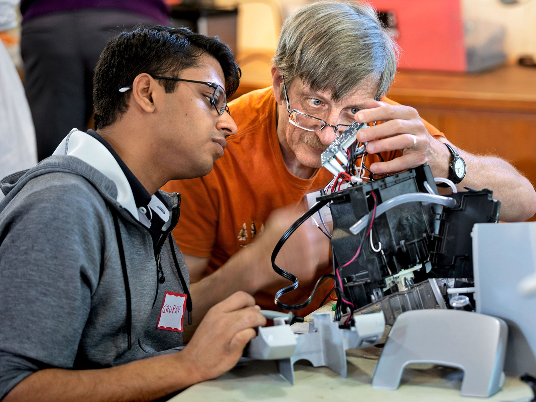 Repair Cafe veteran Joe Margevicius and apprentice Gaurav Aggarwal examine a broken piece of electronics.