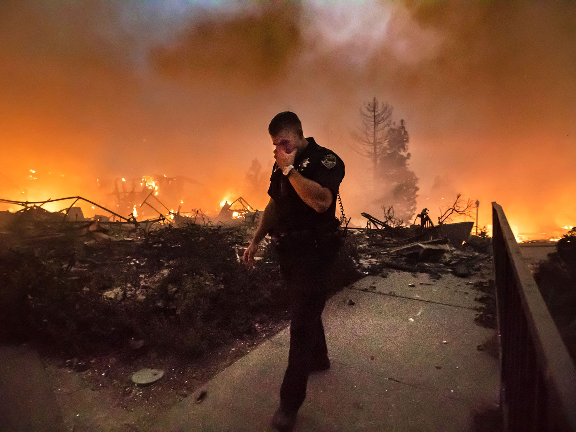San Rafael Police Officer Mark Wilkinson wipes smoke from his eyes as the Santa Rosa Hilton hotel burns behind him on the evening of last Oct. 9.