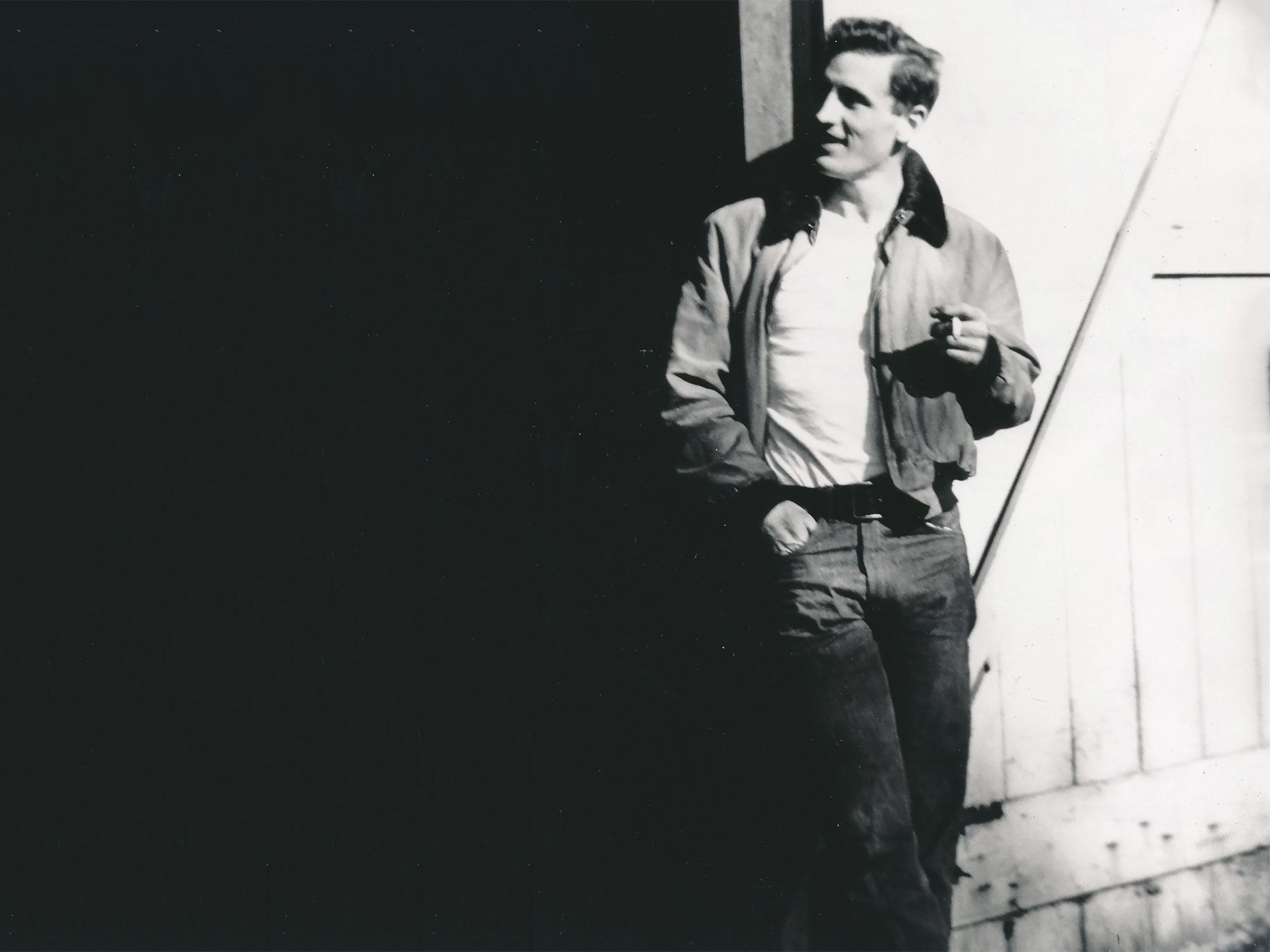 Neal Cassady leans against a door, holding a cigarette, the epitome of Beat-era cool.