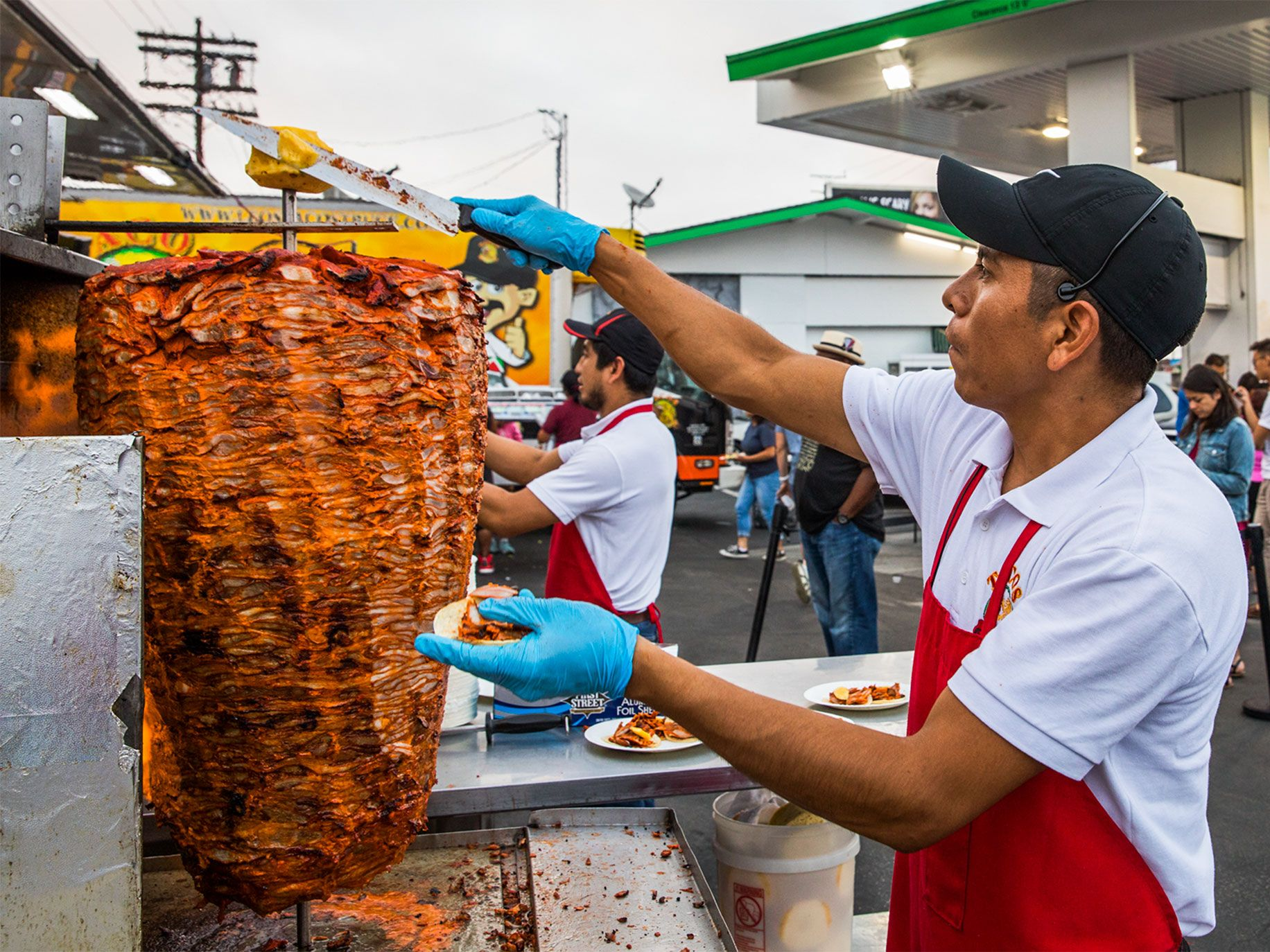 A worker slices off a piece of pineapple atop a spit of al pastor marinated pork on a vertical grill at Leo's Taco Truck.