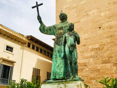 The bronze statue at the entrance of the basilica at Palma de Mallorca, Spain, depicts Father Junípero Serra brandishing a crucifix as his left hand rests on the shoulder of a naked boy.