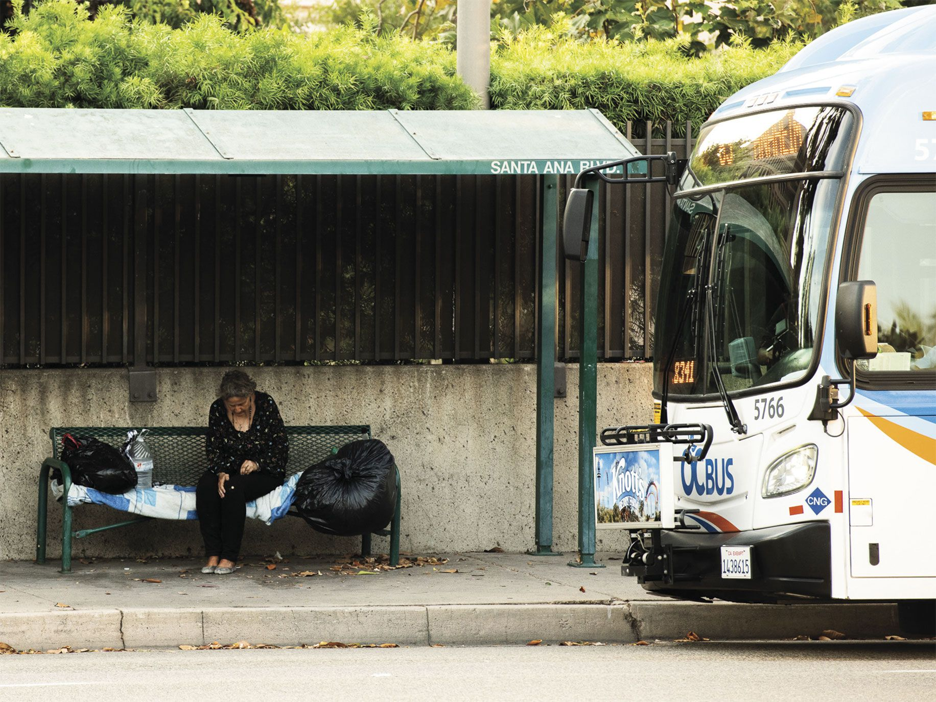 Like most of California, Orange County is seeing an increase in homeless people, like this woman camped out at a bus stop.