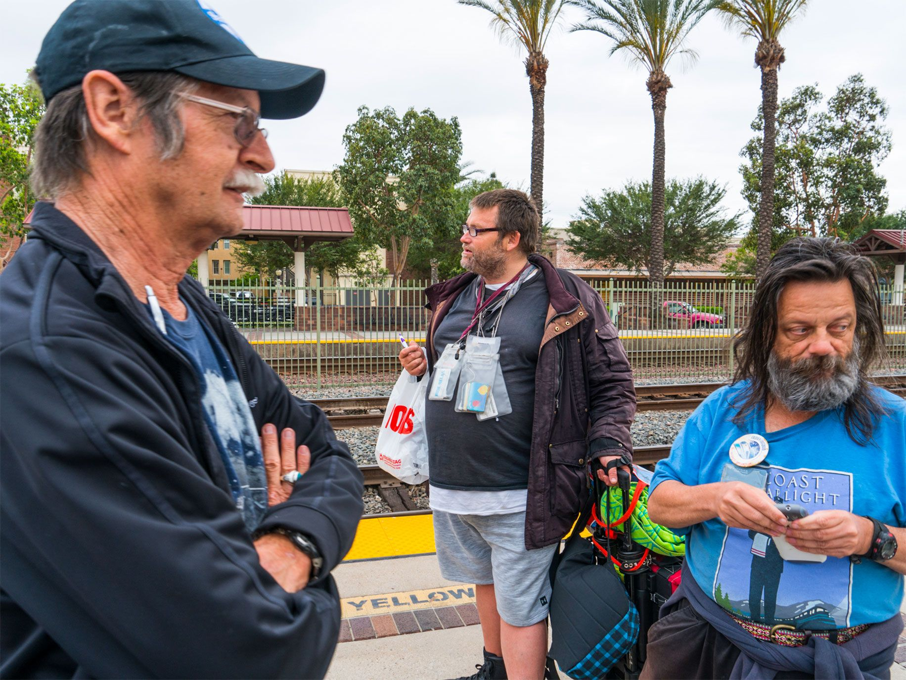 From left, railroad buffs David Aten, Peter Warner and Rick Ivonovitch wait by the tracks for the arrival of the Southwest Chief at the Amtrak station in Fullerton.
