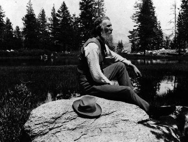 John Muir seated on rock with lake and trees in background.