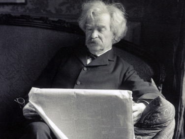 Portrait photograph of Samuel Langhorne Clemens, more popularly known as Mark Twain, seated, reading a newspaper.