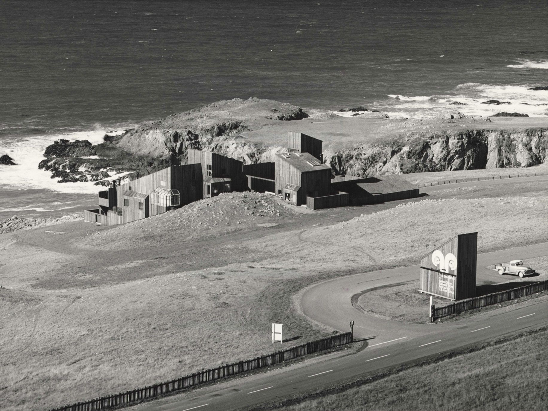 Located on a high bluff above the seashore, surrounded by open space, Condominium One required a design for a clustered mass rather than individual units sprinkled across a landscape. The marker building in the foreground along Highway 1 was photographed in 1965.
