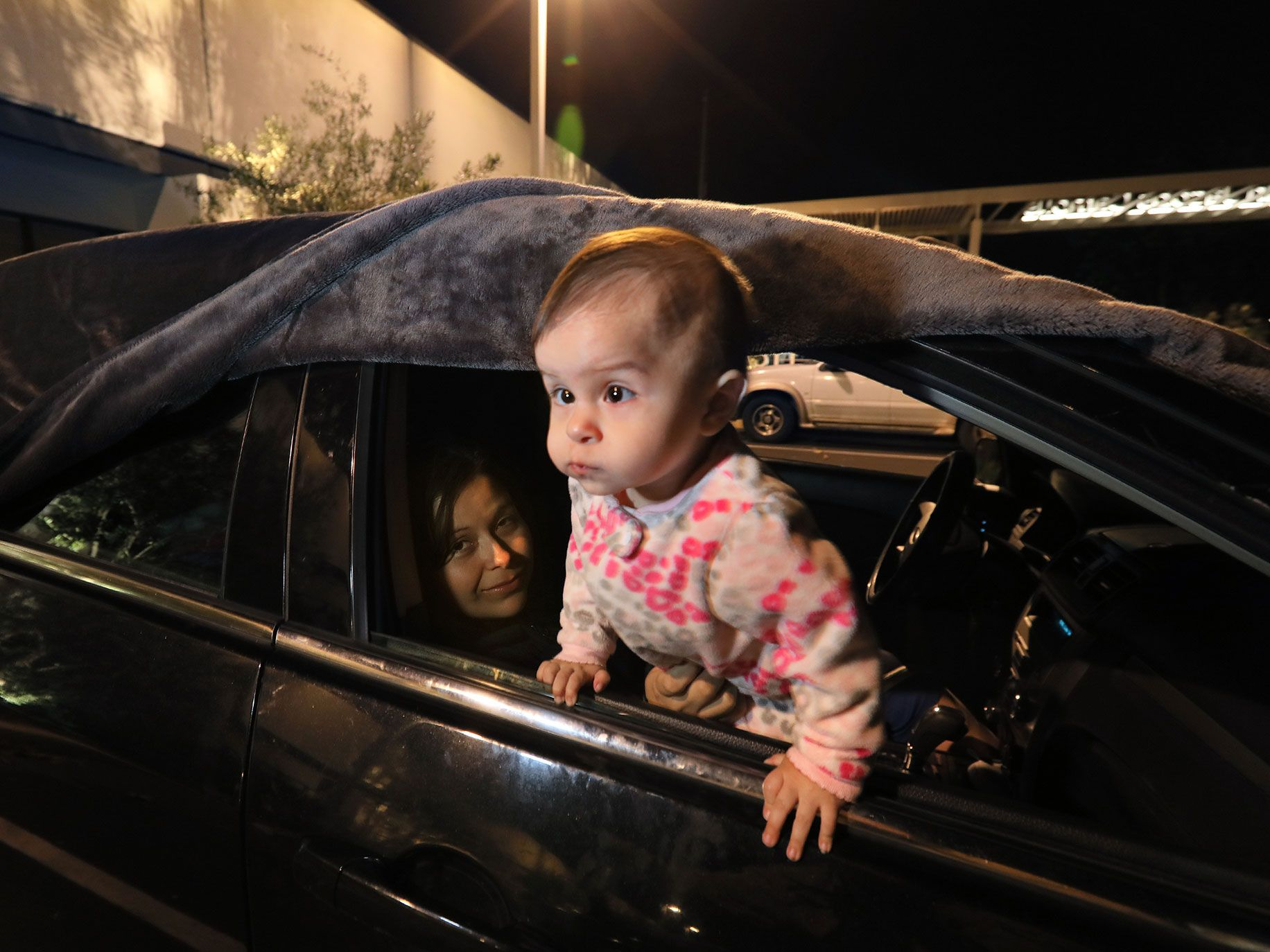 Selena Rivera, held by mom Bertha, looks out the window before Bertha and husband Manuel cover it with the blanket above to spend the night here. Manual has to work in the morning at his security guard job, and the family sleeps in their car in the parking lot of Jewish Family Service of San Diego.