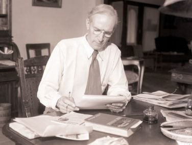 Upton Sinclair, militant international author and Socialist, who captured the Democratic nomination for Governor of California, reads a paper at a desk in 1934.