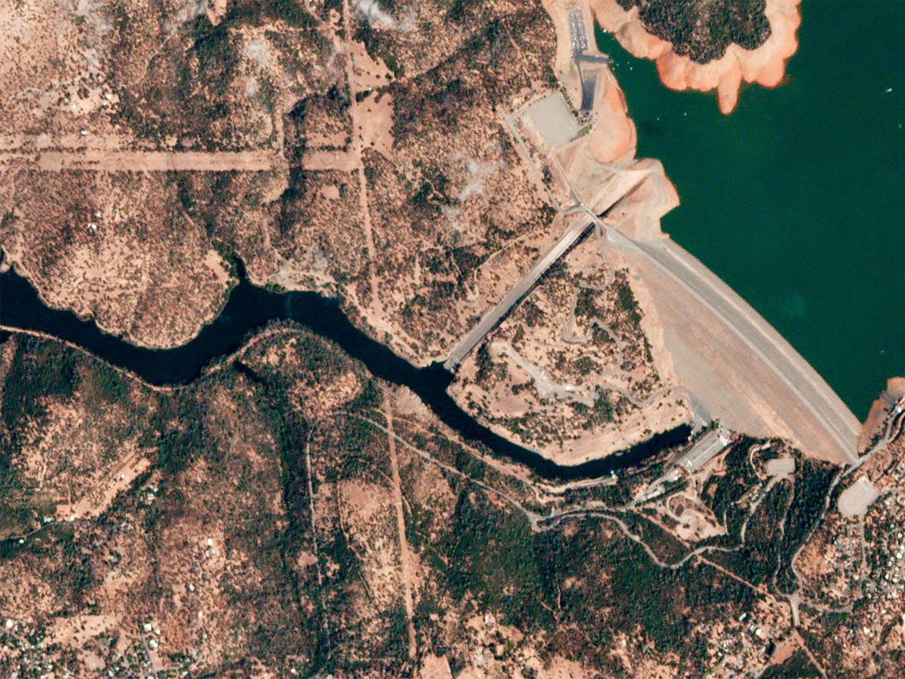 After several years of drought, winter rains filled reservoirs throughout California in February 2017. At the Oroville Dam (the tallest in the United States), water cascaded over the emergency spillway, eroding the surrounding hillside and threatening the town of Oroville and other communities along the Feather River. This satellite imagery sequence shows the dam in drought conditions (top); with water flowing over the damaged spillway during the crisis (middle); and after water levels lowered (bottom).