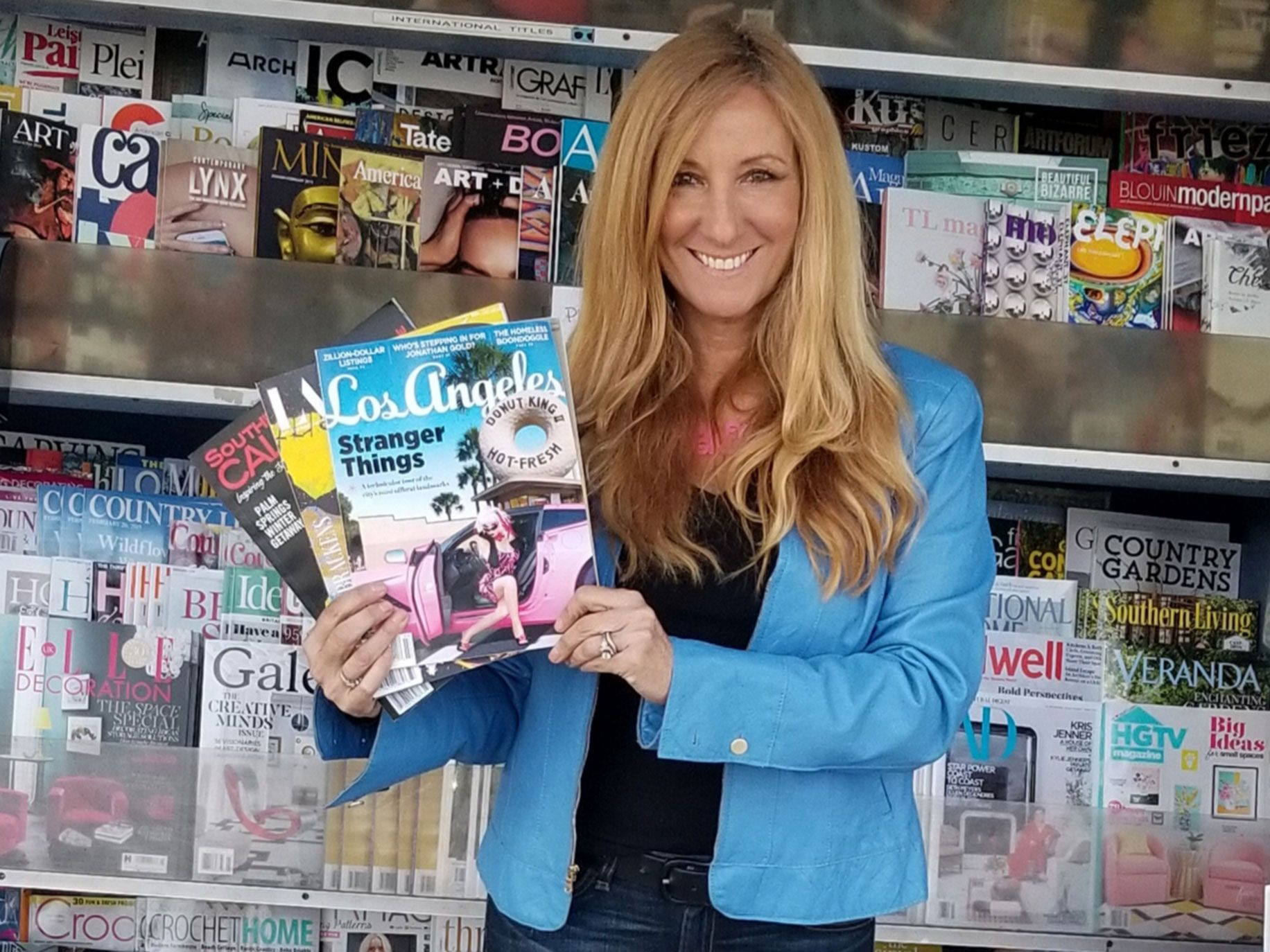 Laurel Canyon News owner Desiree Levine holds up three of her favorite Los Angeles-based magazine