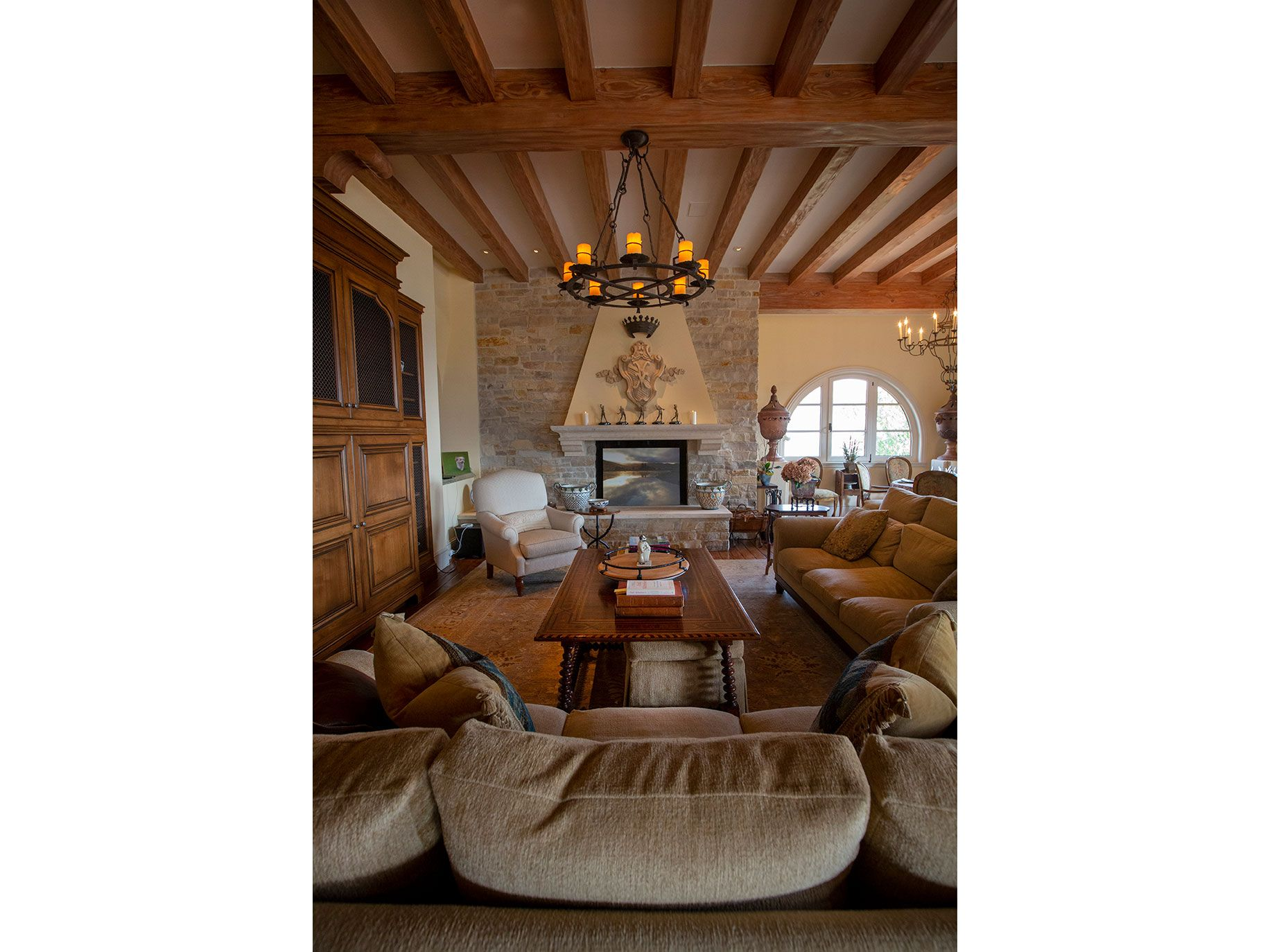 A rustic chandelier hangs from wooden beams above one of the many rooms in the Cheng estate.