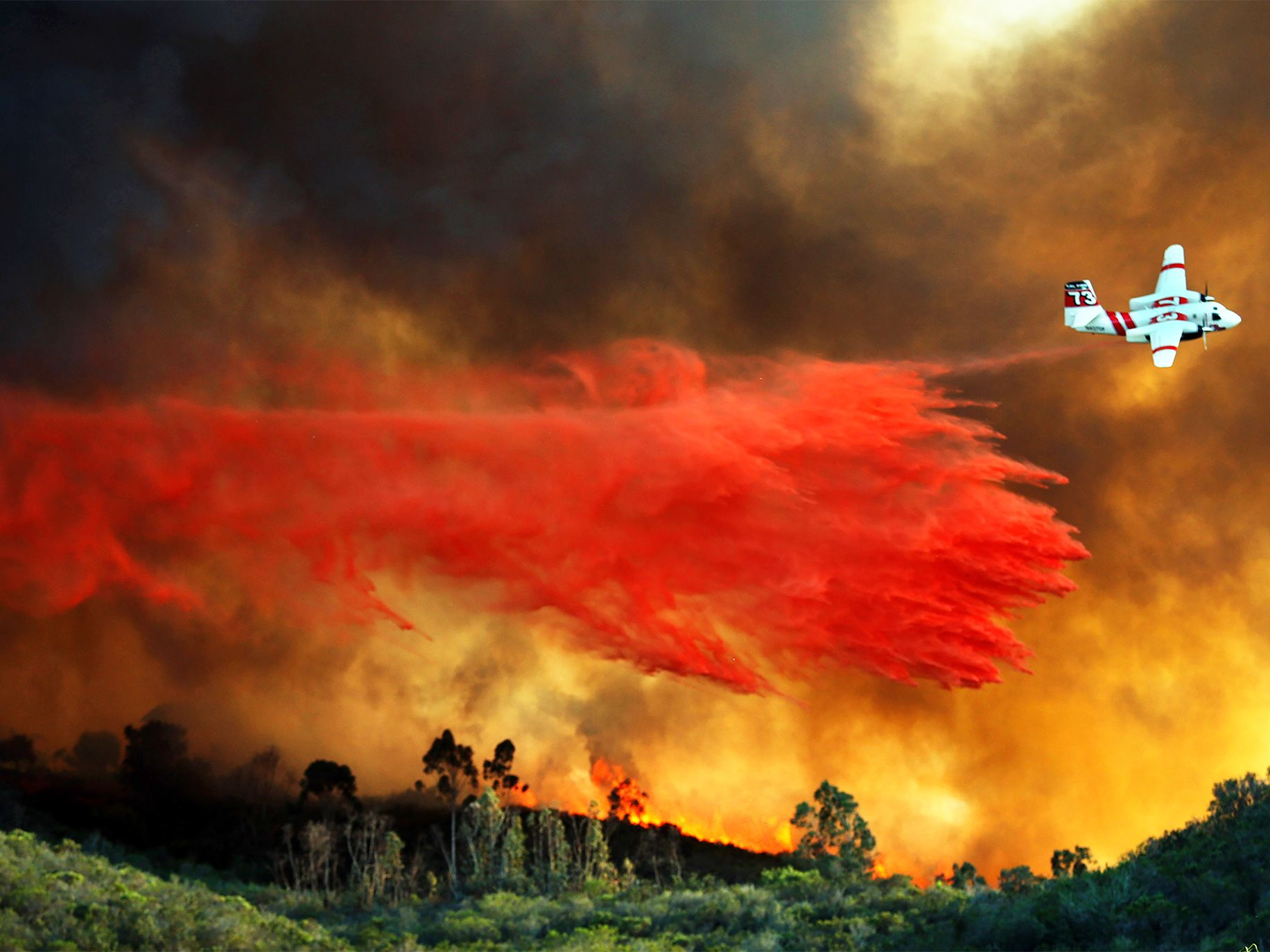 A Cal Fire airplane drops retardant on a large hilltop home that caught fire during a 2014 wildfire in San Marcos.