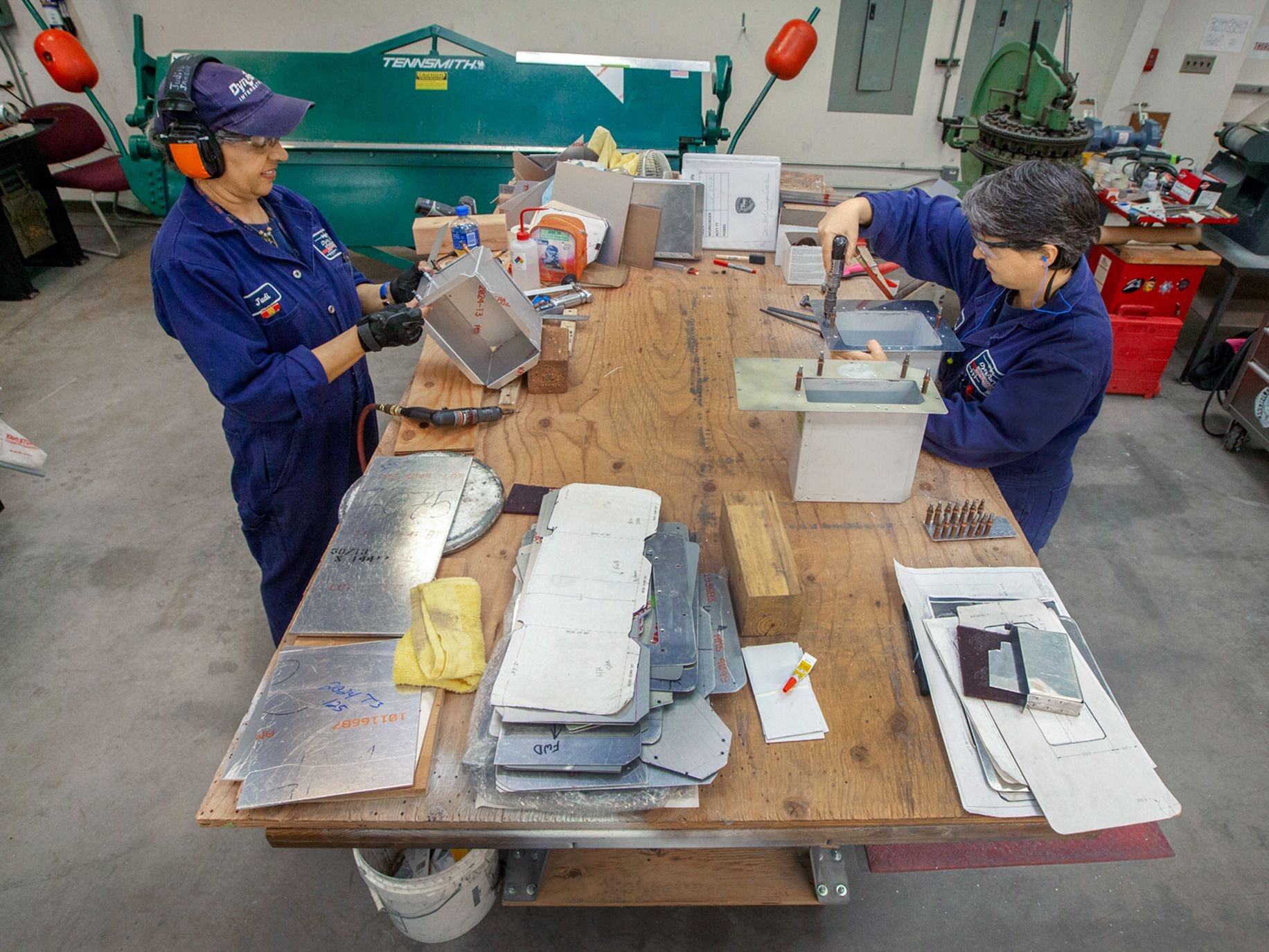 Sheet metal smiths Judi Janelle (left) and Kelly Greco fabricating sheet metal storage boxes for installation in the S2-T air tankers.