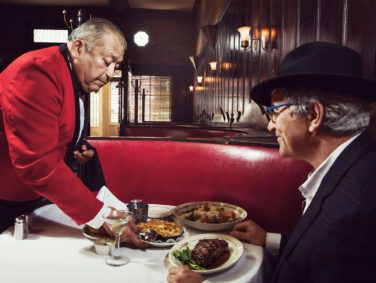 Sergio Gonzales, one of the longest-tenured servers at Musso's, delivers truffled mac and cheese, crab Louie, and grilled New York steak to a hungry Anniversarist.
