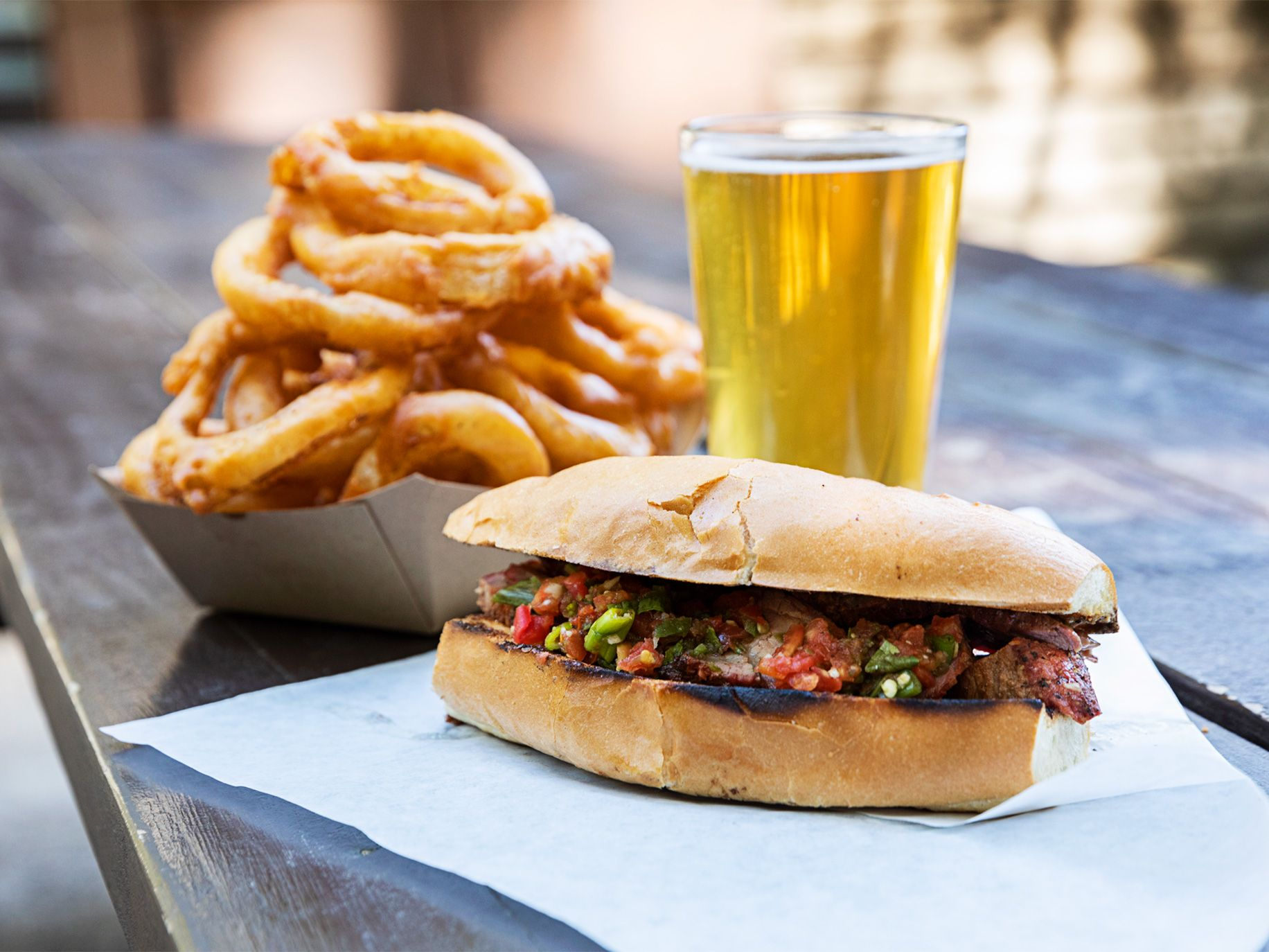 A tri-tip sandwich, onion rings, and draft beer make for simple pleasure.
