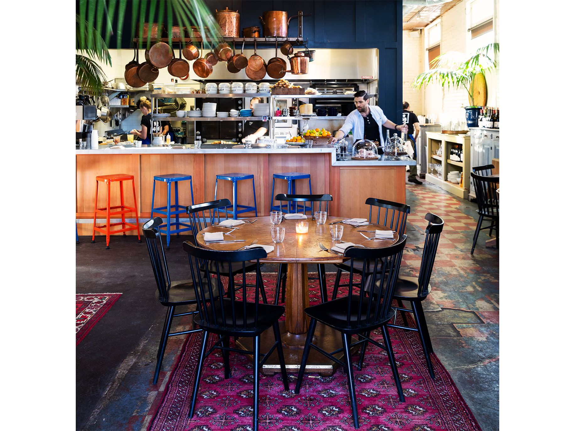 Located in a former Bank of Italy building, the dining room includes exposed brick walls and Oriental rugs partly covering a floor of hardened black tar and old linoleum.