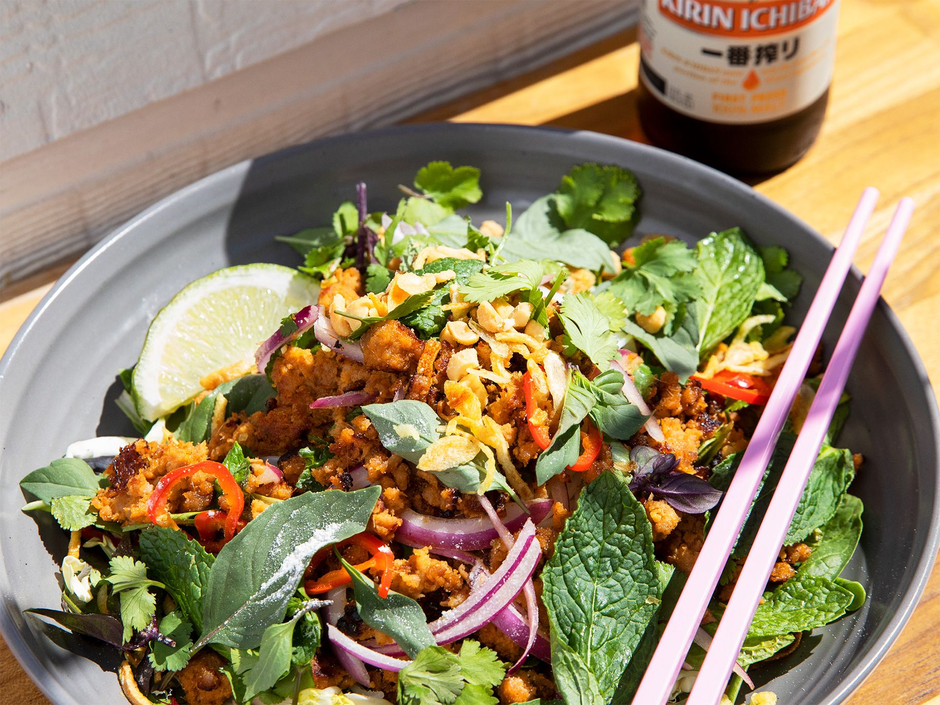 The pork larb noodle bowl, made with minced pork, vermicelli, mixed lettuce, peanuts, chiles, and fried shallots, sits ready to be washed down with a cold beer.
