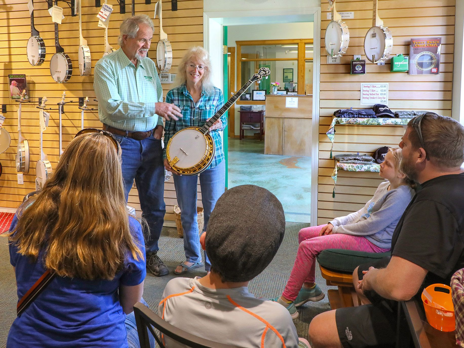 In the display room of the Deering Banjo Company Greg and Janet Deering speak with a family from Tucson, Arizona that are about to take a tour of the facility. The banjo Janet is holding is an Ivanhoe Gold model. At left are the company's Goodtime line of banjos.