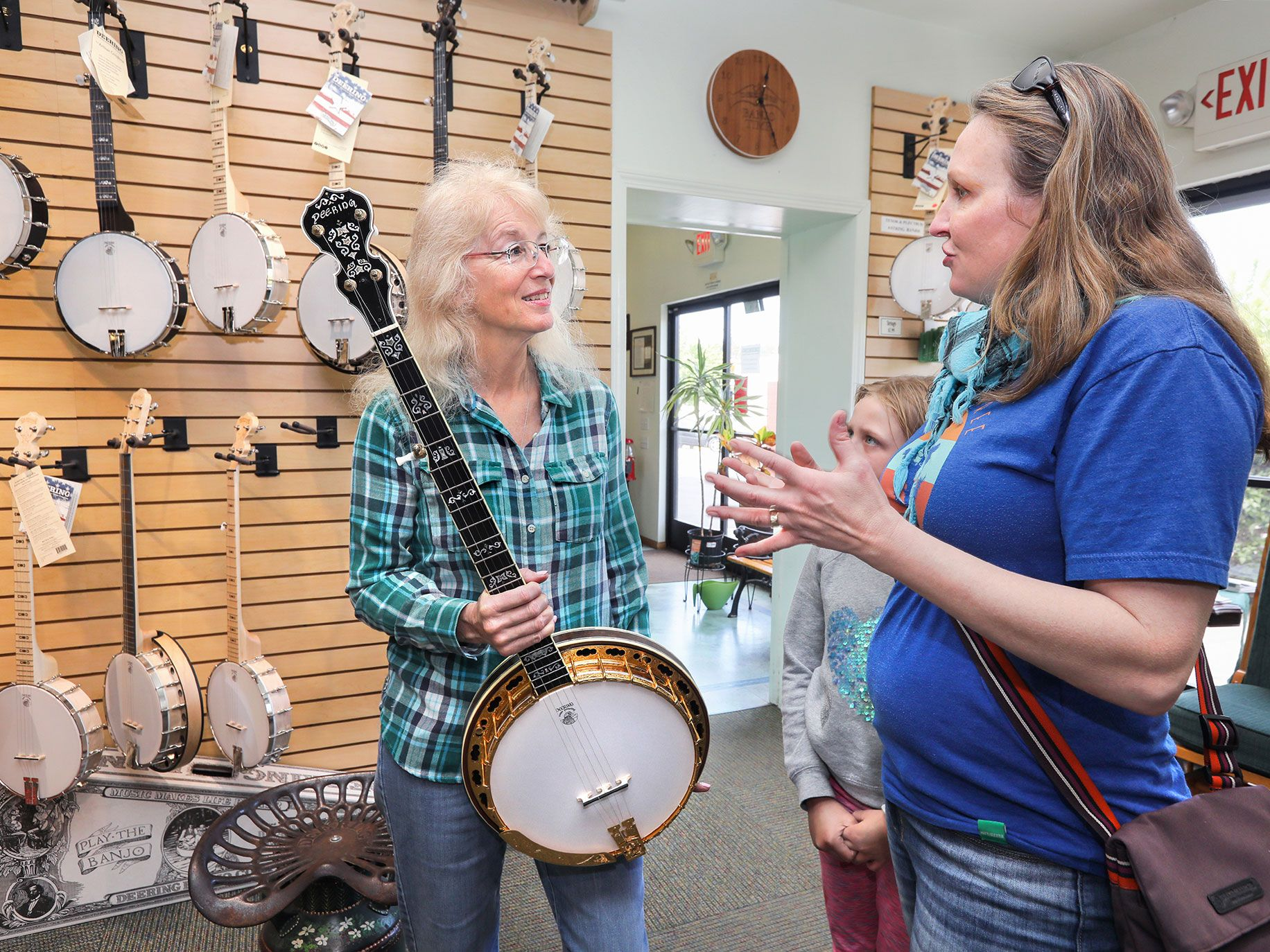 In the display room at the Deering Banjo Company Janet Deering speaks to visitors Jennifer Allison and daughter Aislyn, 8. They and other family members there are from Tucson, Arizona and are about to take a tour of the facility. Janet is holding an Ivanhoe Gold model. At left are the company's Goodtime line of banjos.