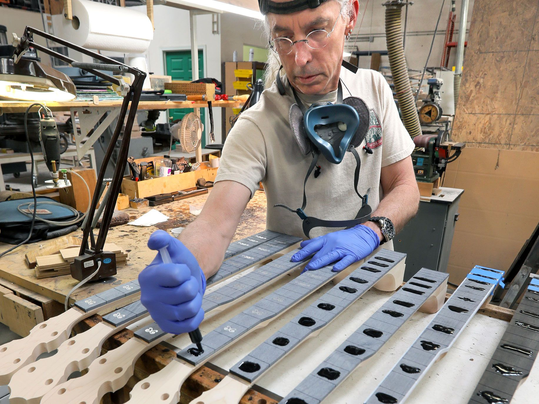 Marty Moore, a longtime employee of the Deering Banjo Company, applies epoxy resin for the intricate fret inlays for banjo fingerboards.