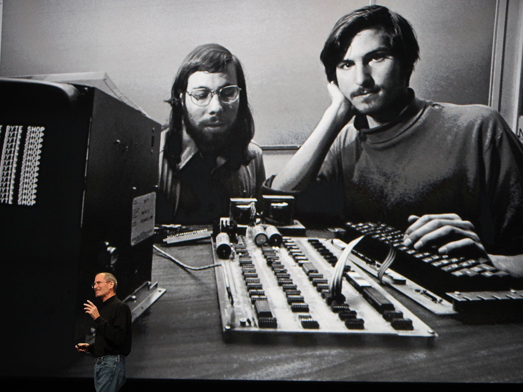 Steve Jobs speaks in front of a file photograph of himself and Apple co-founder Steve Wozniak with the first Apple computer.