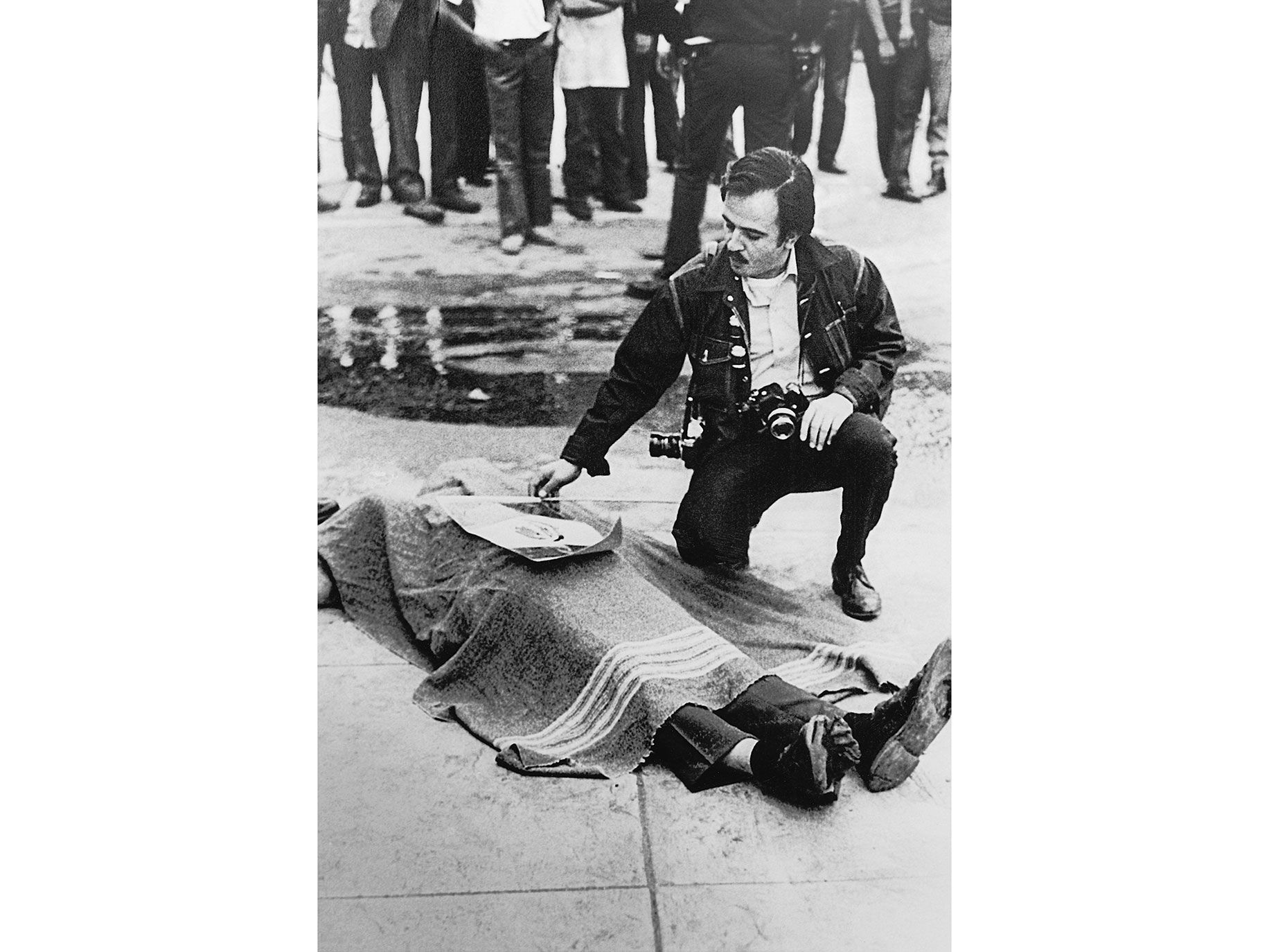Raul Ruiz lays a Mexican flag atop the corpse of Gustav Montag, a bystander slain by ricochet ammunition during a 1971 protest in East Los Angeles.
