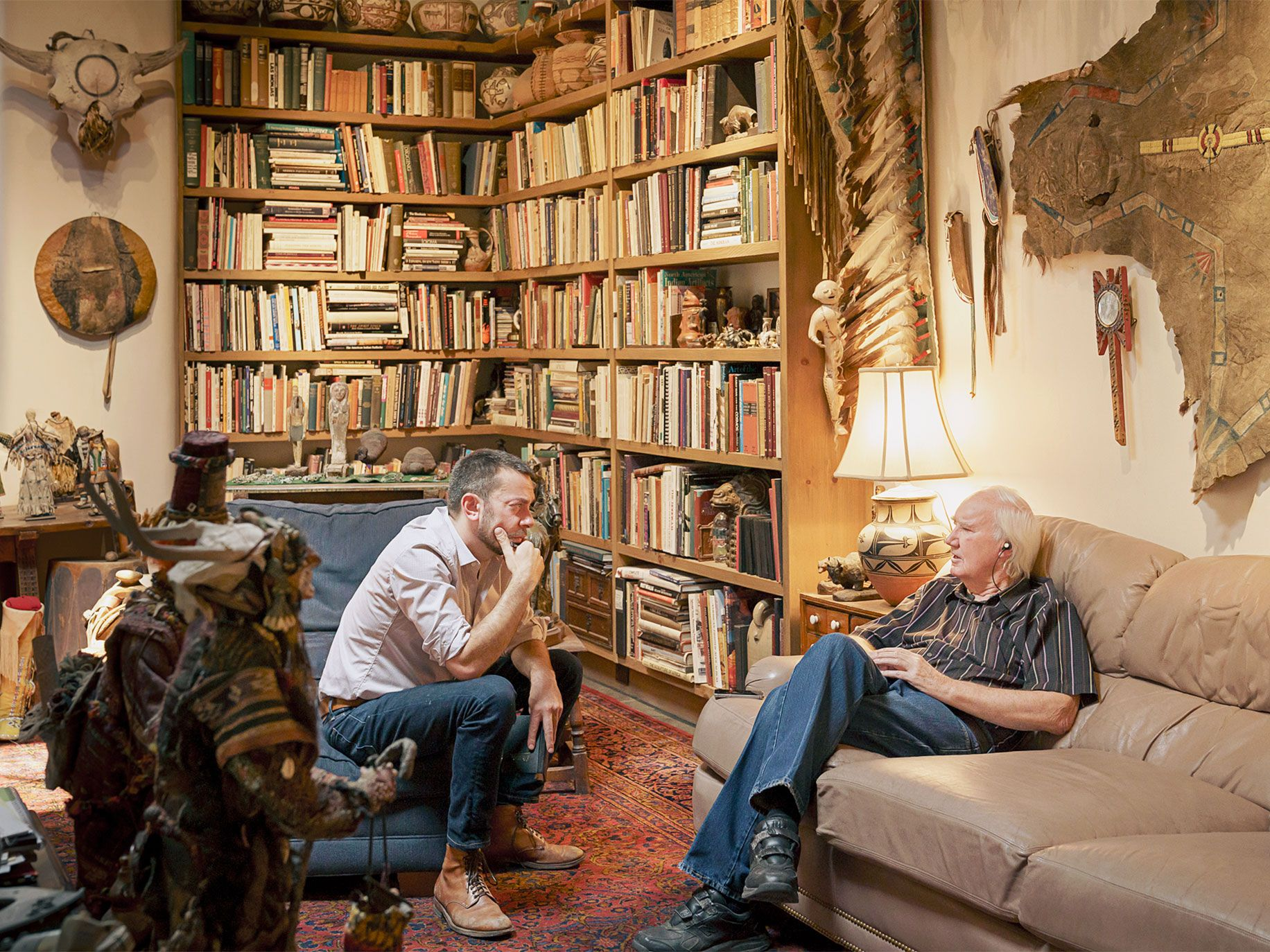 Geoffrey Gray interviewing Forrest Fenn in Fenn's study, which is filled with his collection of Native American artifacts.