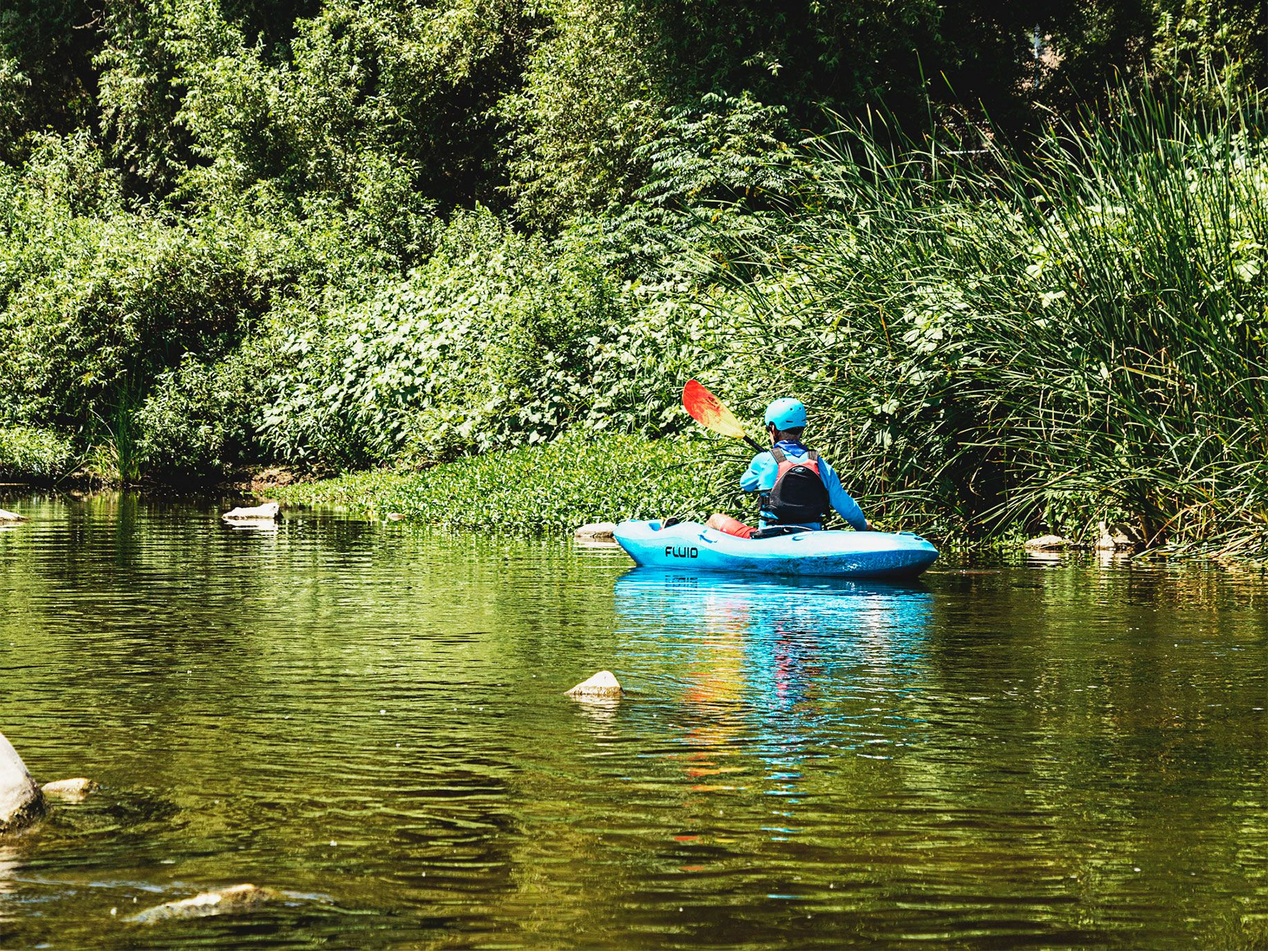 Here, a kayaker paddles through a lush section of river in the Frogtown neighborhood. Architect Frank Gehry's plans to revitalize the river include a series of wide elevated platforms that would provide parkland and outdoor space for social, cultural, and recreational activities.