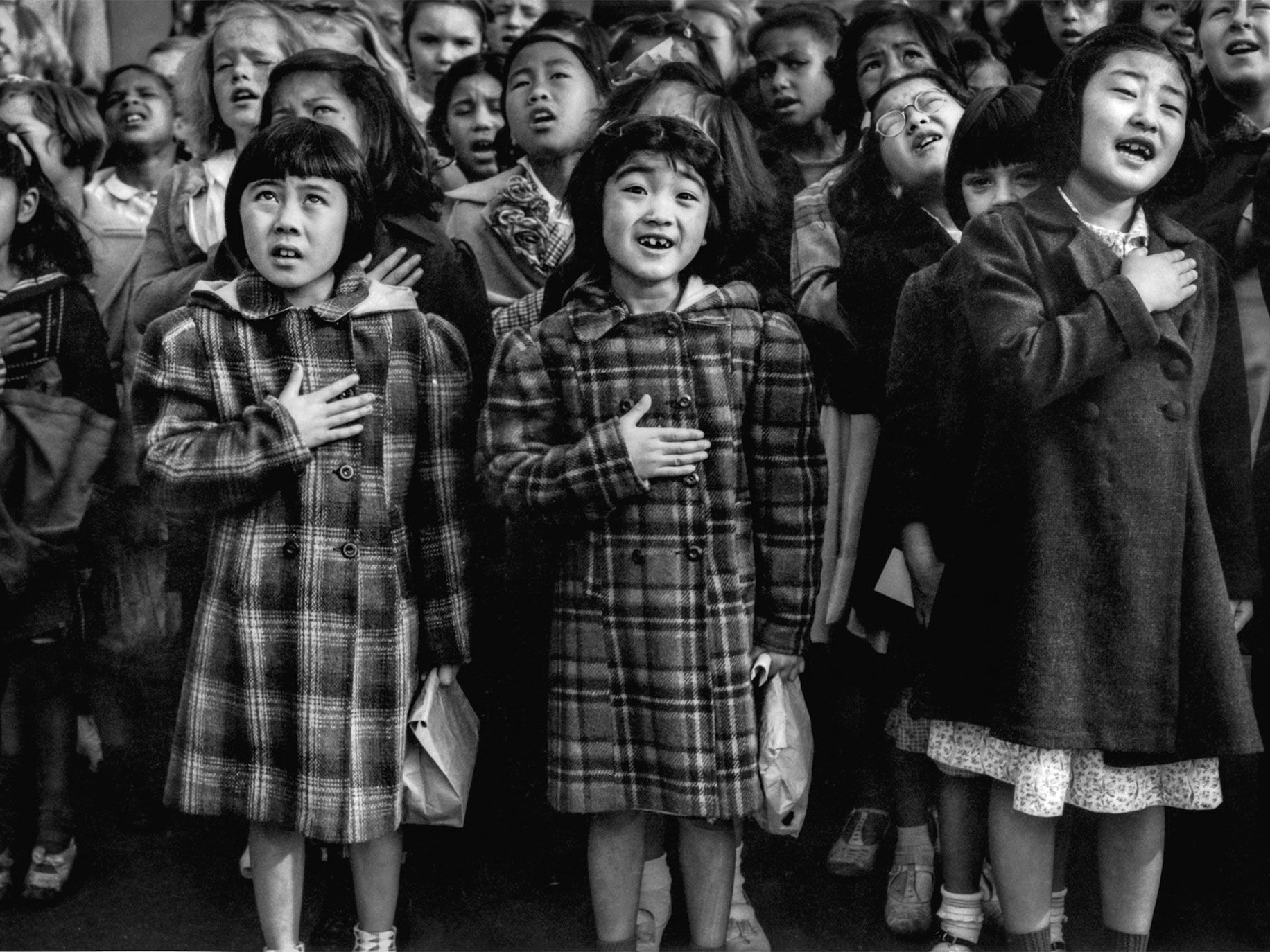 "Seven-year-olds Hideno Nakamoto (left) and Yoko Itashiki (center) pledge allegiance at Raphael Weill School in 1942 before being sent to an assembly center and eventually transferred to the Topaz War Relocation Center, in Utah. Itashiki's mother was sent to a camp in Pacifica, California, where she died. ""It was pretty traumatic because her body came back, and we had a funeral in Topaz,"" Itashiki said. ""It was really hard for me being a child seeing her like that when I hadn't seen her in a long time."""