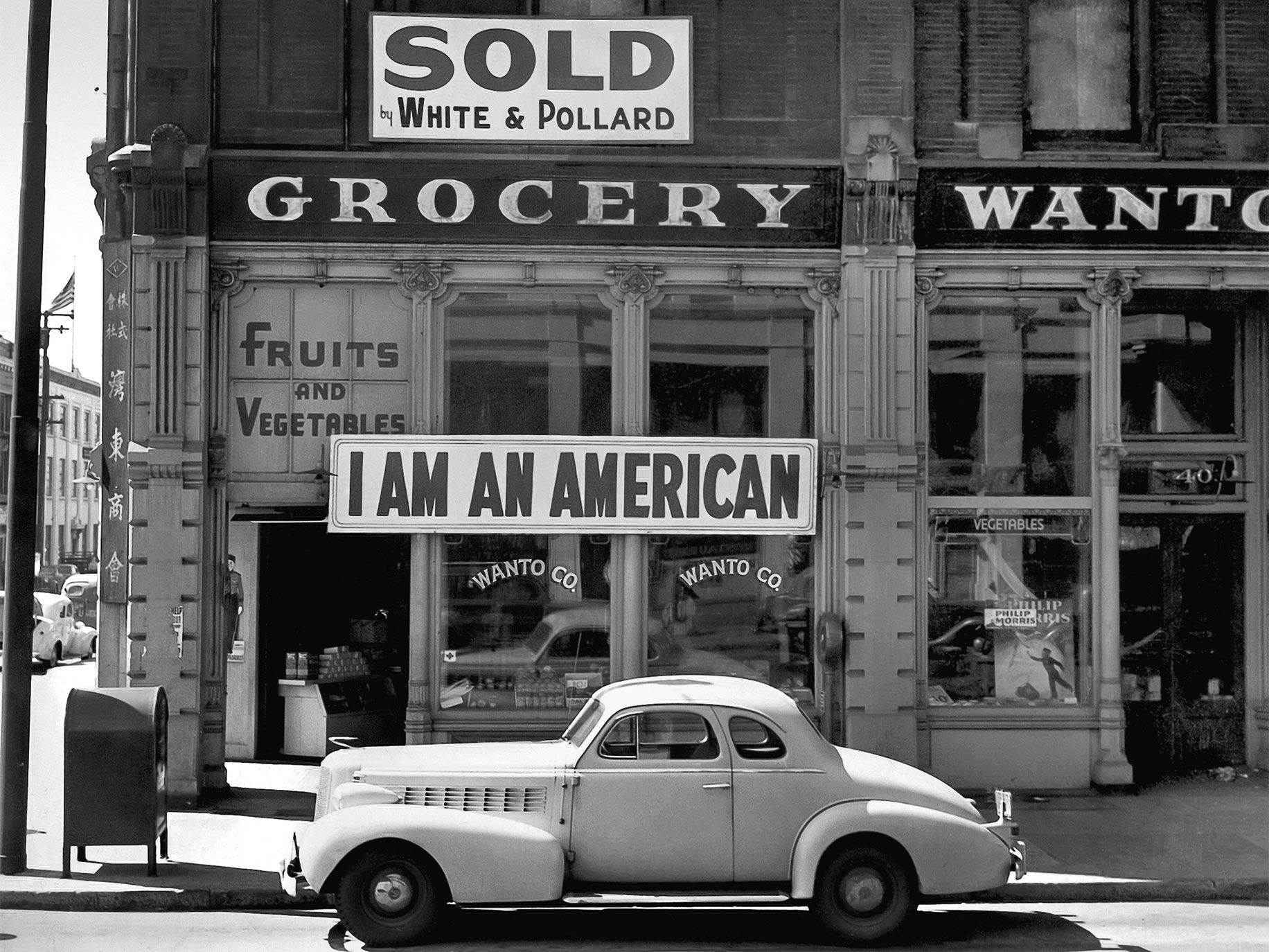 "Below: Owned by the Masuda family, the Wanto Shokai grocery store was located in downtown Oakland. Tetsuo Masuda, a graduate of UC Berkeley, took over the business after his sisters, Mineko and Yoshiko, were sent to an internment camp. Tetsuo created the ""I Am an American"" sign in 1943. The remaining family members moved to Fresno County, hoping they would not be evacuated. The whole family ended up at the Gila River Relocation Center, in Arizona."