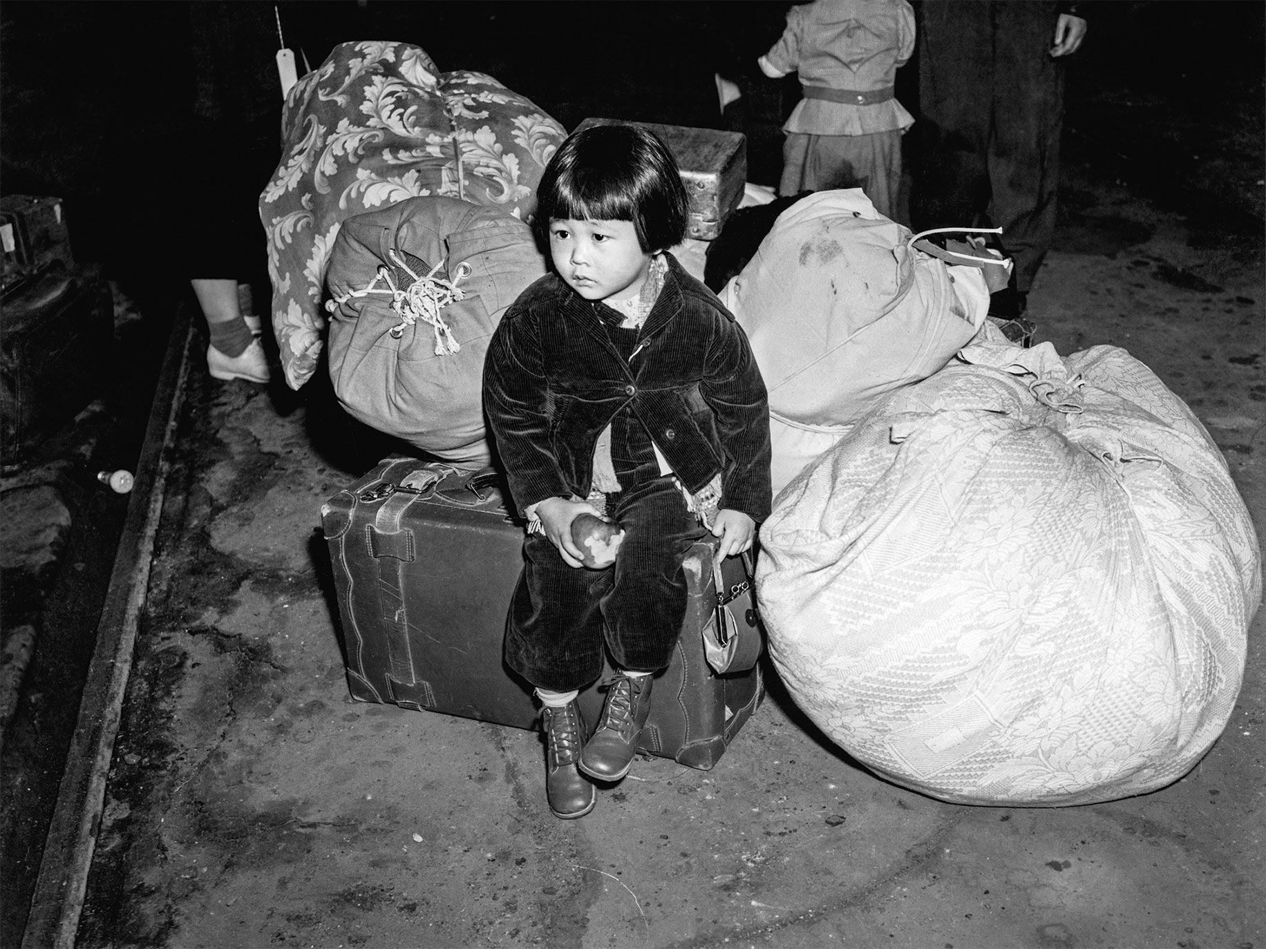 "Holding an apple, two-year-old Yukiko Okinaga Hayakawa sits with her luggage at Union Station, in Los Angeles, in 1942 after she and her single mother are forced to leave their home in Little Tokyo. They would spend three years at the Manzanar War Relocation Center, in California. ""She got me this red corduroy outfit, and that's what I am wearing,"" Hayakawa said. ""And she got me those lovely shoes. I said, 'You bought those for me for the evacuation?' She said, 'Yes, because you didn't have anything to wear.' And I thought, 'How many people did that?' "" Hayakawa learned English after the war when she and her mother relocated to Cleveland, where her mom supported the family as a seamstress. ""When I went to school in Cleveland, people yelled at me and called me names,"" she said. "" 'There goes that dirty Jap.' And I didn't know what that meant. My mom would say, 'Well, that's the way it goes. Shikata ga nai.' """