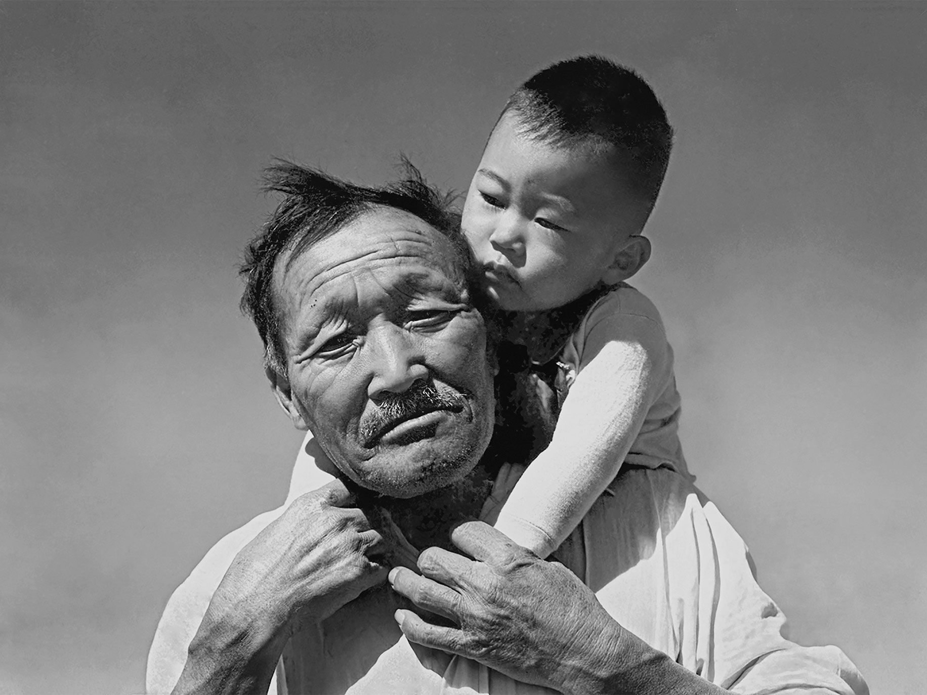 "Walter Yoshiharu Sakawye, 17 months old, hangs off the back of his paternal grandfather, Torazo Sakawye, at the Manzanar War Relocation Center, in California, in 1942. Walter was born in East Los Angeles in 1941, and his father was a trucker in Venice, California, hauling produce from the fields to a market downtown. The family owned a double lot, with a house on one lot and three trucks on the other. When they returned after the war, the trucks and all their tools were gone. Torazo was a truck farmer who had immigrated to the United States from Japan in 1902. He died in the internment camp at age 68. ""He passed away, I think, more or less of a broken heart,"" Walter says. ""In the picture, he just appears to be saying, 'What'd I do? Why am I here?' """