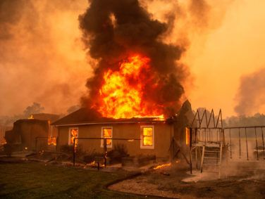 A home burns at a vineyard during the Kincade fire near Geyserville, California on October 24, 2019. - fast-moving wildfire roared through California wine country early Thursday, as authorities warned of the imminent danger of more fires across much of the Golden State. The Kincade fire in Sonoma County kicked up Wednesday night, quickly growing from a blaze of a few hundred acres into an uncontained 10,000-acre (4,000-hectare) inferno, California fire and law enforcement officials said.
