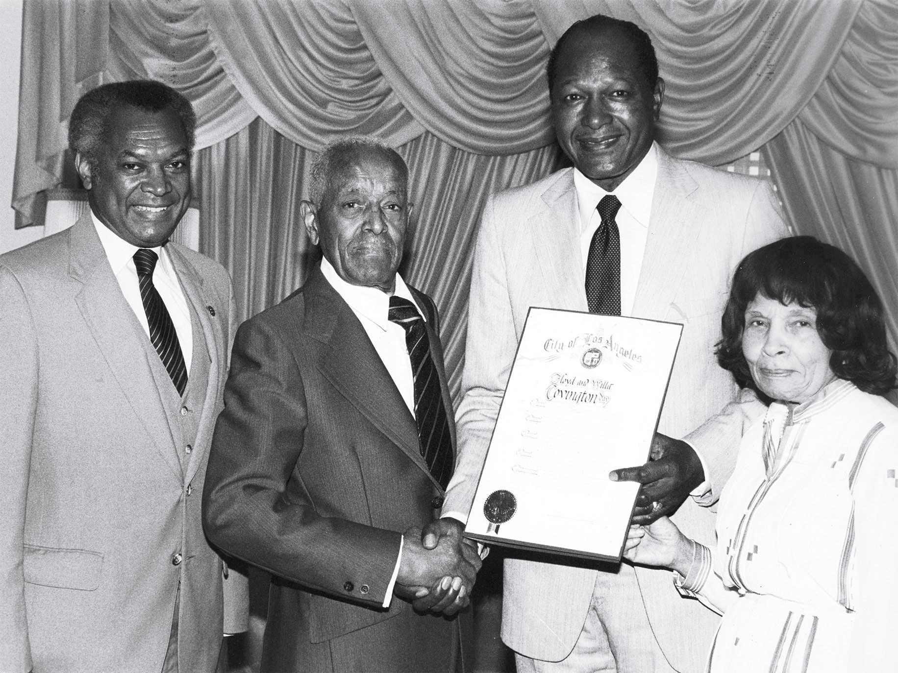 L.A. mayor Tom Bradley holds a certificate declaring April 24, 1984, as Floyd and Alma Covington Day; he's joined by John Mack (far left), then president of the Los Angeles Urban League.