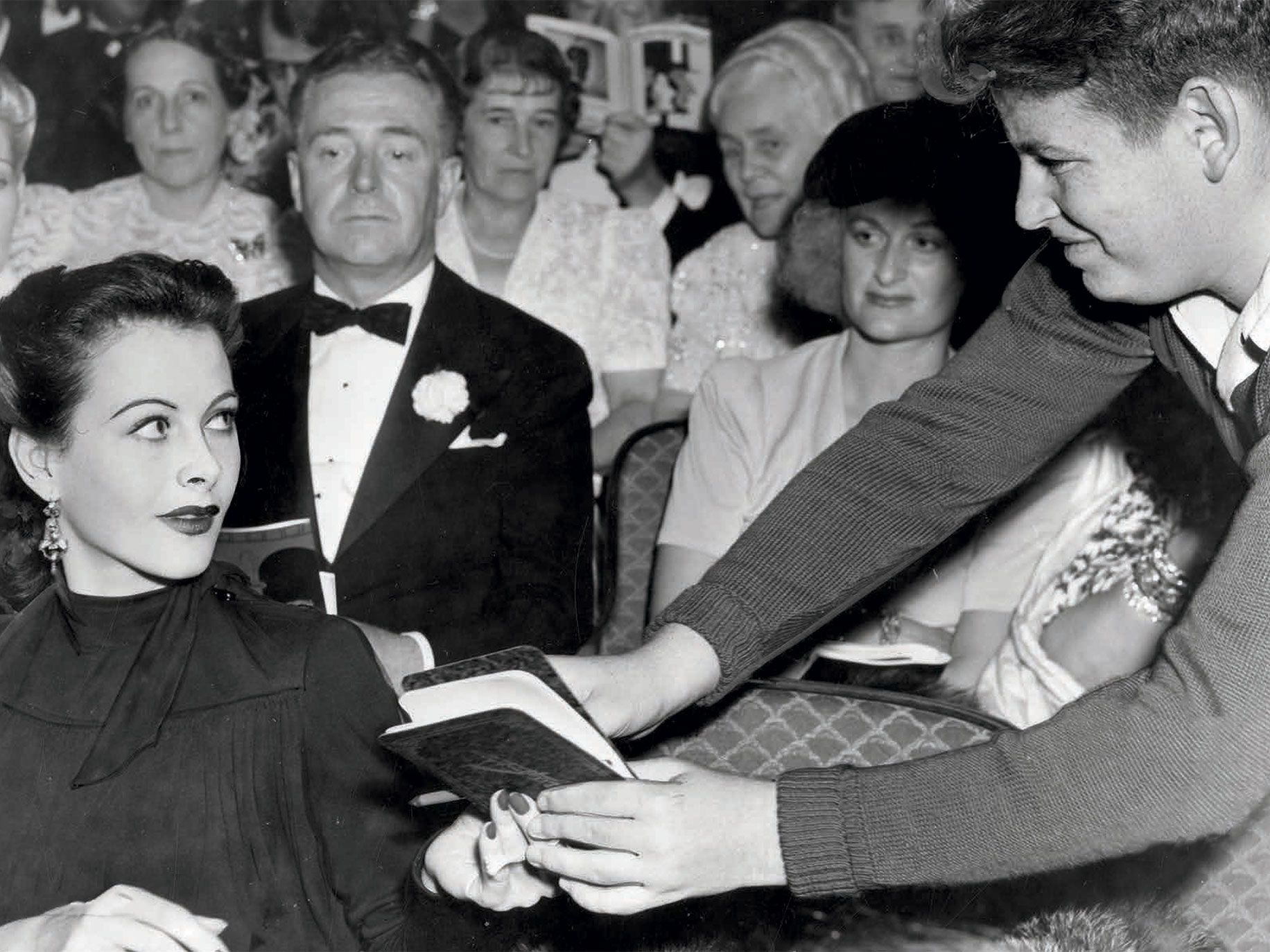 Hedy Lamarr signs an autograph book at the El Capitan Theatre in Hollywood, 1940. Photo from The Autograph Book of L.A.: Improvements on the Page of the City.