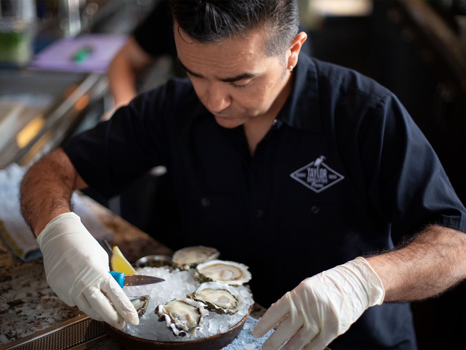Louis Morales, general manager at Taylor Shellfish in Pioneer Square, prepares a Shucker's Dozen plate.