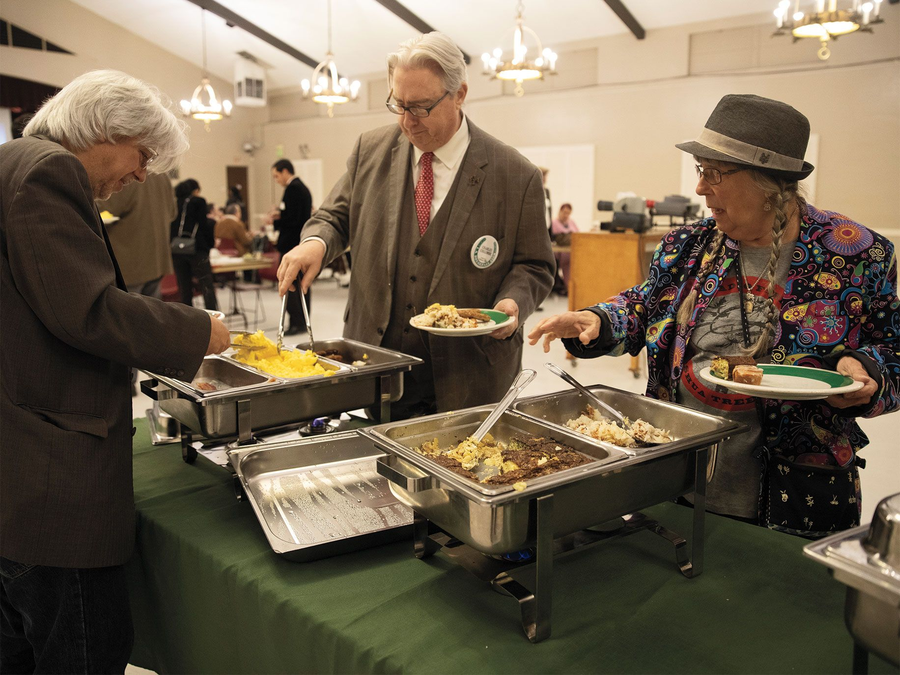 Members Charles Coulombe (center) and Jenifer Palmer Lacy (right) dig into a catered hot breakfast.