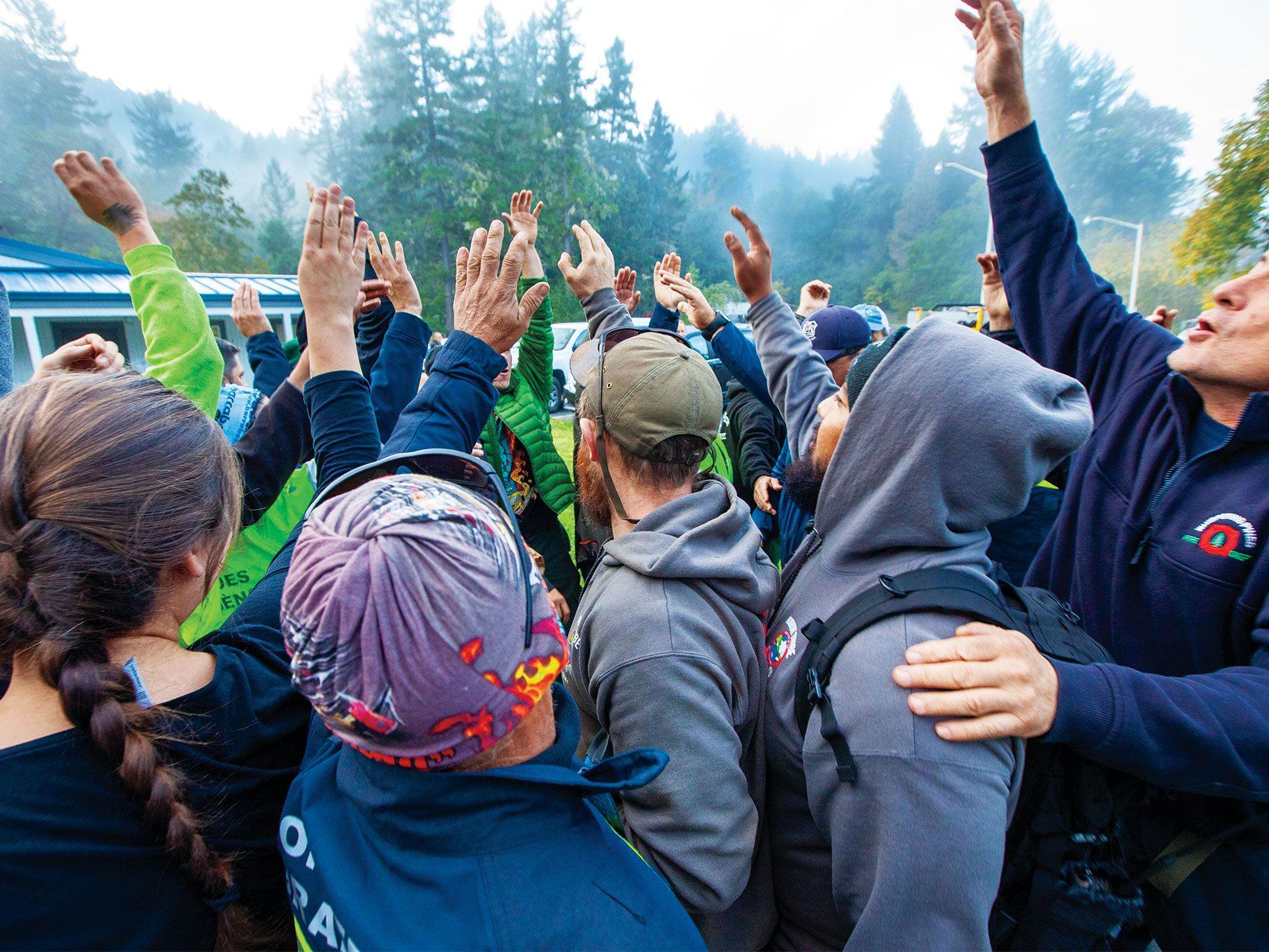 """One of the teams participating in a TREX burn raise their hands in unity following an early morning meeting. Most of those who will set fires must pass a """"pack test"""" by hiking three miles in 45 minutes while carrying 45 pounds."""
