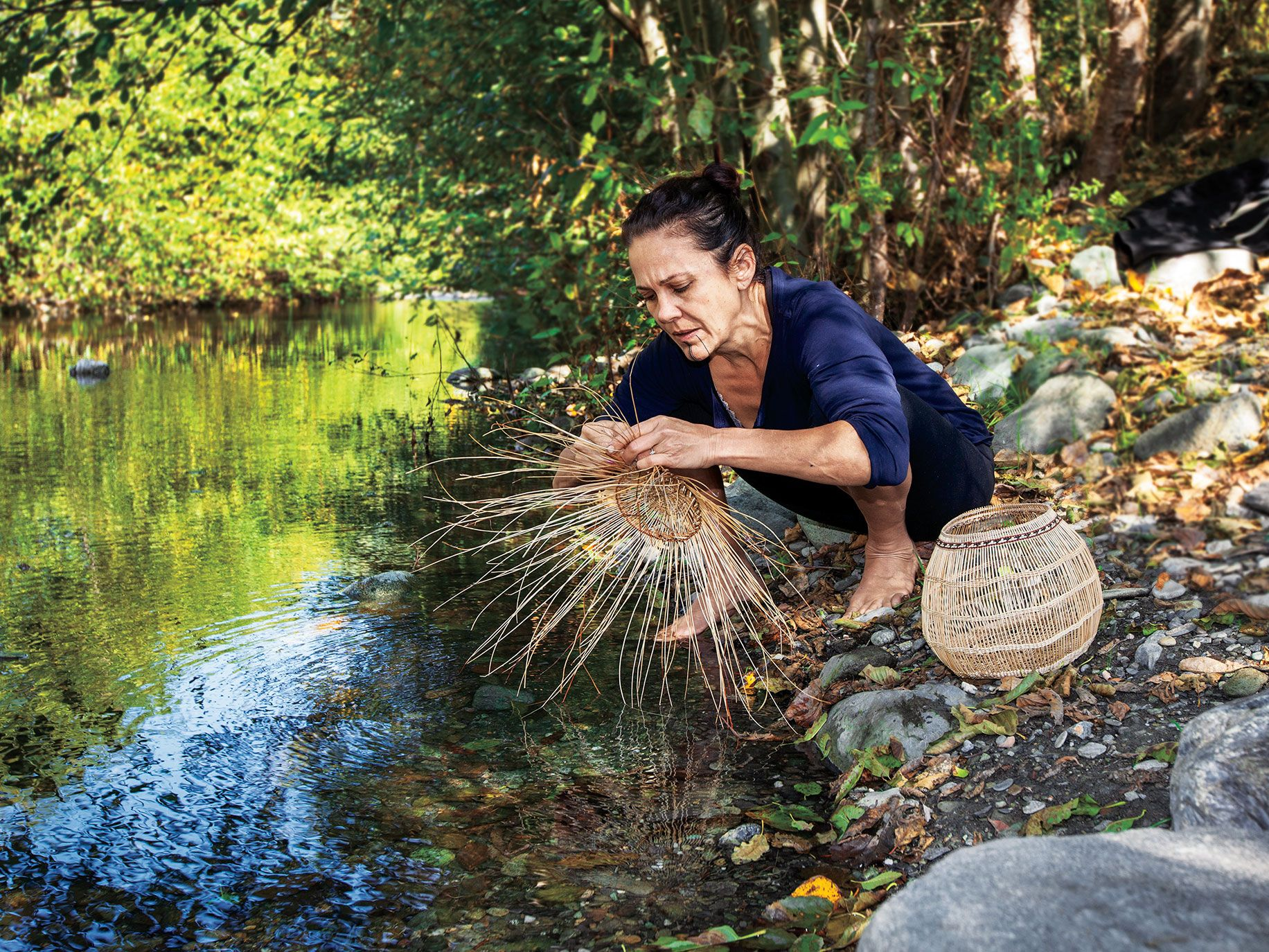 Lisa Hillman, a Pikyav Field Institute program manager, weaves plant materials that she dunks in water to make them more pliable. After a burn, the new shoots of hazel shrubs are sought by basket makers.