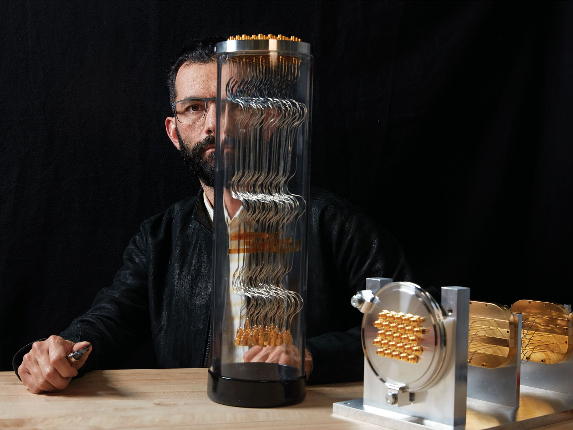 Google research scientist Erik Lucero with a quantum computer's vacuum feedthrough, which holds coaxial cables used to carry microwave pulses to and from its processors.
