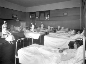 Nurses wearing breathing masks administer to patients in the ward, believed to be the isolation ward at Pasadena's Wilson High School during the 1919 influenza epidemic.