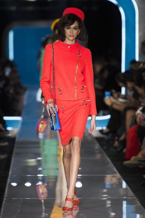 Fashion show, Shoulder, Red, Outerwear, Runway, Human leg, Fashion model, Style, Fashion accessory, Hat,