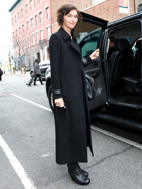 Standing, Coat, Style, Vehicle door, Automotive exterior, Street fashion, Street, Overcoat, Blazer, Luxury vehicle,