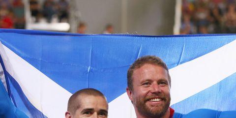 Smile, Award, Facial expression, Electric blue, World, Medal, Cobalt blue, Award ceremony, Gesture, Flag,