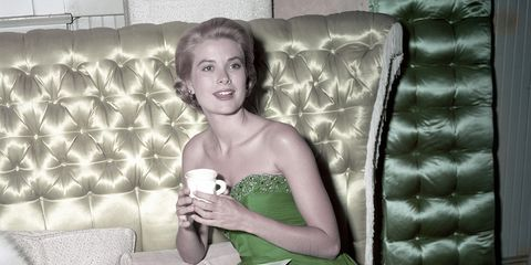 Green, Dress, Textile, Room, Interior design, Style, Couch, Strapless dress, Sitting, Comfort,